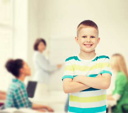 childhood, school, education and people concept - smiling little boy in casual clothes with crossed arms over group of students in classroom Stock Photo