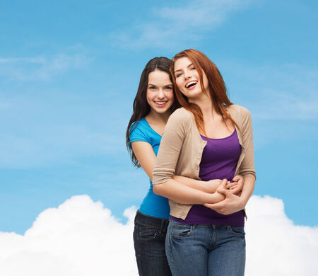 hispanic students: happiness, friendship and people concept - smiling teenage girls hugging over blue sky and cloud background