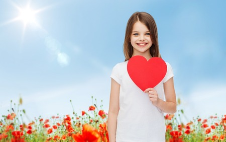 youngsters: love, charity, holidays, children and people concept - smiling little girl with red heart over blue sky and poppy field background