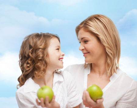 over eating: people, family, healthy eating and parenting concept - happy mother and daughter with green apples over blue sky background