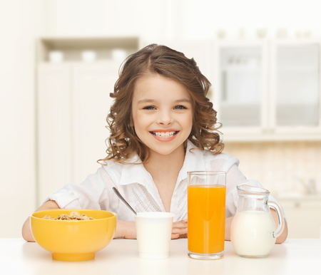 children breakfast: healthy food, eating, people and children concept - happy smiling beautiful girl having breakfast over home kitchen background