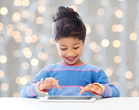 asian children: education, children, technology and people concept - happy little girl with tablet pc computer over holidays lights background