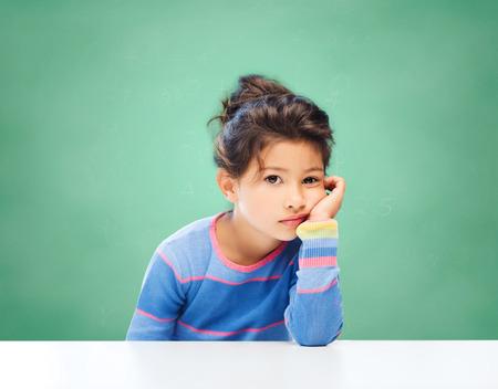 교육, 사람들, 어린 시절 및 감정 개념 - 녹색 분필 보드 배경 위에 슬픈 또는 지 루 작은 학교 소녀