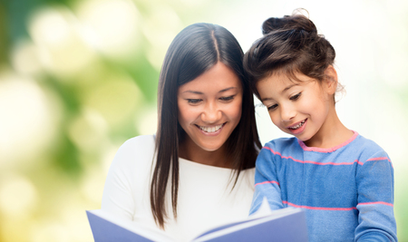 family, children, education, school and happy people concept - happy mother and daughter reading book over green background photo
