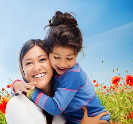 asian child: people, happiness, love, family and motherhood concept - happy mother and daughter hugging over blue sky and poppy field background Stock Photo