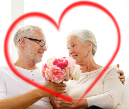 family, holidays, age and people concept - happy senior couple holding bunch of flowers at home with big red heart shape photo