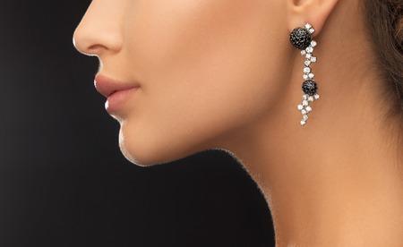 美しさとジュエリーのコンセプト - 光沢のある身に着けている女性はダイヤモンド イヤリング