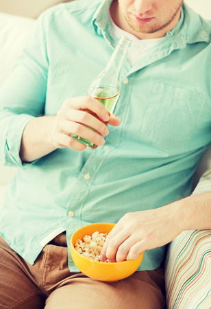 nonalcoholic beer: food, drinks, relax, leisure and people concept - close up of man with popcorn and beer sitting on couch at home Stock Photo