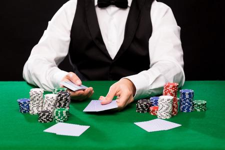 カジノ、火かき棒、人々、エンターテイメントの概念 - はトランプと緑のテーブル上のチップのホールデム ディーラーのクローズ アップ 写真素材