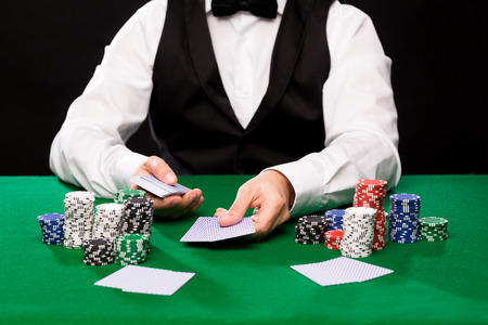 hold em: casino, gambling, poker, people and entertainment concept - close up of holdem dealer with playing cards and chips on green table
