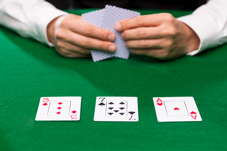 seven persons: casino, gambling, poker, people and entertainment concept - close up of poker player holding playing cards at green casino table