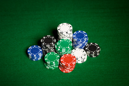 gambling, fortune, game and entertainment concept - close up of casino chips on green table surface photo