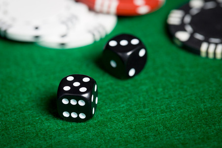 odds: gambling, fortune, game and entertainment concept - close up of black dices on green casino table
