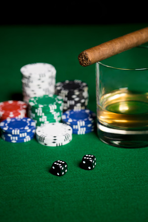 double the chances: gambling, fortune and entertainment concept - close up of casino chips, whisky glass, dice and cigar on green table surface Stock Photo