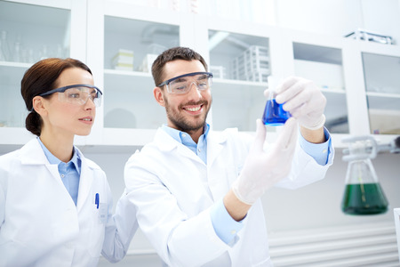reagents: science, chemistry, technology, biology and people concept - young scientists holding flask with reagents and making test or research in clinical laboratory Stock Photo