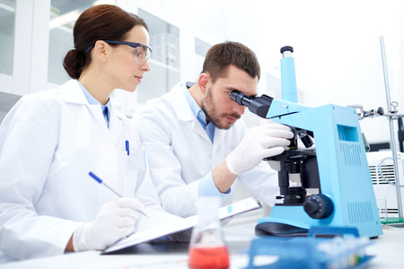 science, chemistry, technology, biology and people concept - young scientists with microscope making test or research in clinical laboratory and taking notes