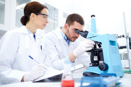 química: ciencia, química, tecnología, biología y concepto de la gente - los científicos jóvenes con microscopio haciendo pruebas o investigación en laboratorio clínico y tomar notas Foto de archivo