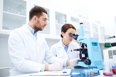ciencia, química, tecnología, biología y concepto de la gente - los científicos jóvenes con microscopio haciendo pruebas o investigación en laboratorio clínico y tomar notas Foto de archivo