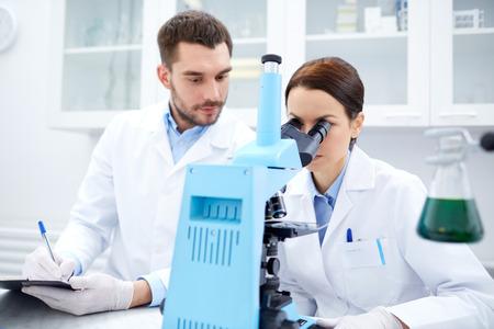 biologia: ciencia, qu�mica, tecnolog�a, biolog�a y concepto de la gente - los cient�ficos j�venes con microscopio haciendo pruebas o investigaci�n en laboratorio cl�nico y tomar notas Foto de archivo