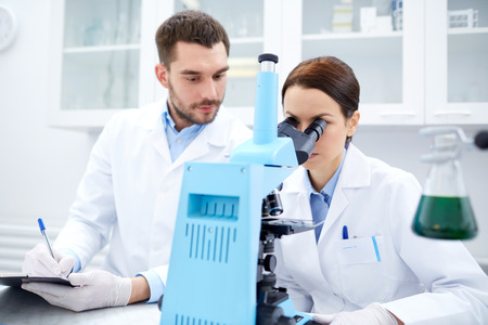 biology: science, chemistry, technology, biology and people concept - young scientists with microscope making test or research in clinical laboratory and taking notes