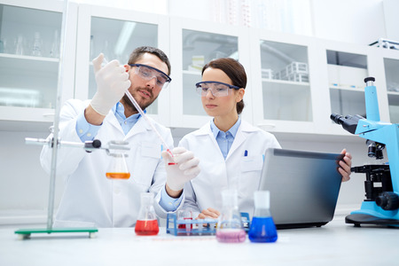 discovering: science, chemistry, technology, biology and people concept - young scientists with pipette and glass making test or research in clinical laboratory