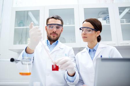 investigación: ciencia, qu�mica, tecnolog�a, biolog�a y concepto de la gente - los cient�ficos j�venes con prueba o investigaci�n pipeta y la fabricaci�n de vidrio en el laboratorio cl�nico