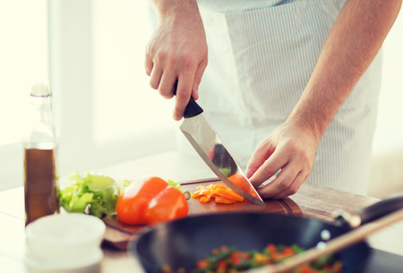 cooking, food and home concept - close up of male hand cutting pepper on cutting board at home photo