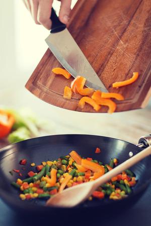 料理、食品、ホーム コンセプト - を鍋に唐辛子を追加する男性の手のクローズ アップ 写真素材