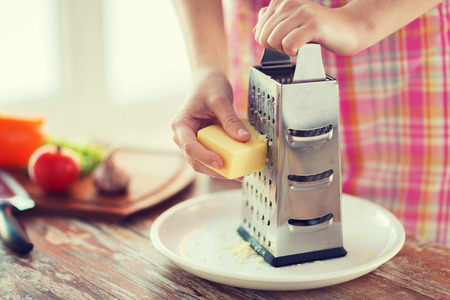 cooking, food and home concept - close up of female hands grating cheese photo
