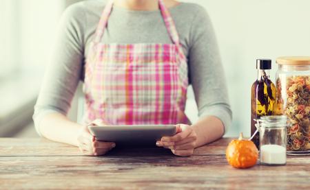 delantal: la cocina, la tecnología y el concepto de casa - de cerca de receta lectura de la mujer de la computadora tablet pc Foto de archivo