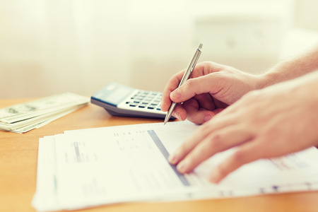 financial paperwork: savings, finances, economy and home concept - close up of man with calculator counting money and making notes at home