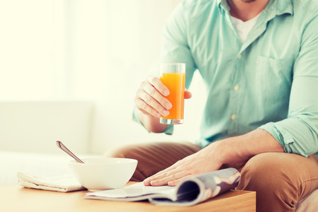 news room: home, news, food, drinks and people concept - close up of man reading magazine and drinking juice sitting on couch at home