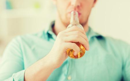 hombre tomando cerveza: bebidas, relax, ocio y concepto de la gente - cerca del hombre bebiendo cerveza sentado en el sofá en casa Foto de archivo