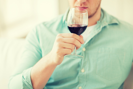 degustating: drinks, relax, leisure and people concept - close up of man drinking red wine and sitting on couch at home
