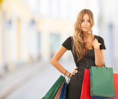 people, holidays and sale concept - young happy woman with shopping bags over city street background photo
