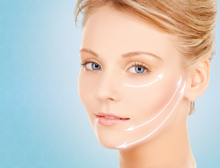 antiaging: beauty and people concept - face of beautiful young woman over blue background