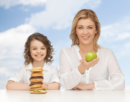 people, healthy lifestyle, family and unhealthy food concept - happy mother and daughter eating different food over blue sky background photo