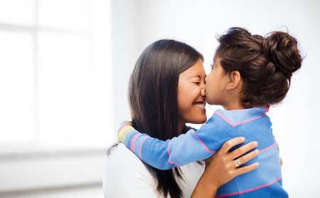 asian child: family, children and happy people concept - happy little girl hugging and kissing her mother over white room background