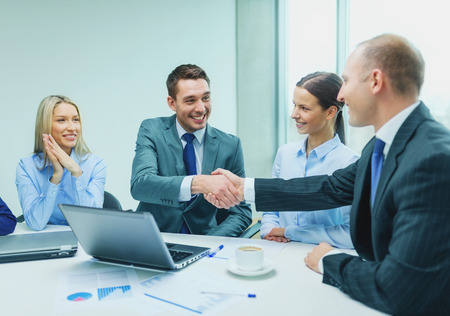 business hand shake: business, technology, partnership and people concept - two smiling businessman shaking hands in office