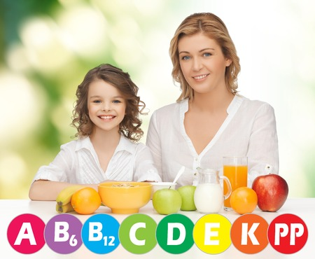 multivitamin: people, healthy lifestyle, family and food concept - happy mother and daughter eating healthy breakfast over green background with vitamins