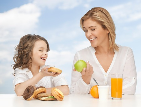 people, healthy lifestyle, family and food concept - happy mother and daughter eating healthy breakfast over blue sky background photo