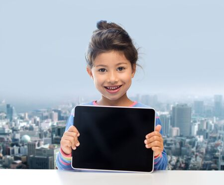 black asian: education, children, technology, advertisement and people concept - happy little girl with tablet pc computer over city background