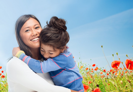 people, happiness, love, family and motherhood concept - happy mother and daughter hugging over blue sky and poppy field background Stock Photo