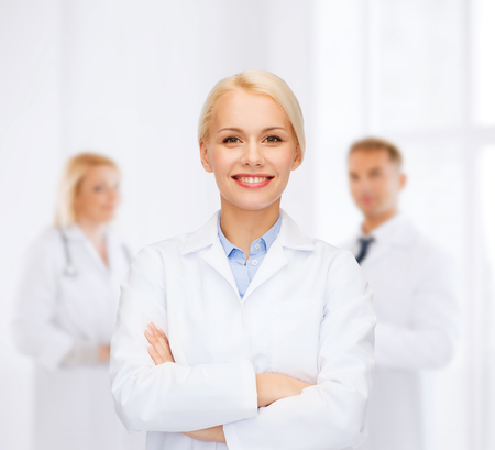 medics: healthcare and medicine concept - smiling female doctor over group of medics in hospital Stock Photo