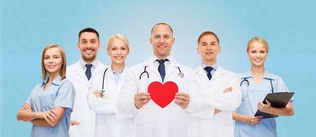 grupo de médicos: la medicina, profesión, trabajo en equipo y el concepto de salud - grupo de sonrientes médicos o doctores que sostienen el corazón de papel rojo shape, portapapeles y estetoscopios sobre fondo azul Foto de archivo