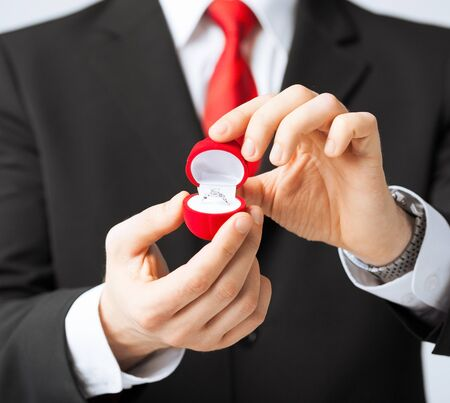 man making proposal with wedding ring in red gift box photo