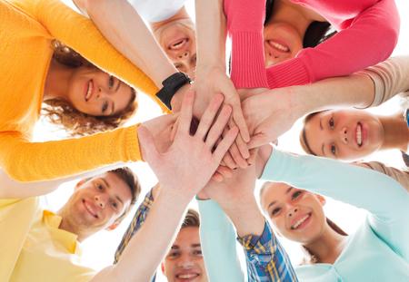 juventud: la amistad, los jóvenes y las personas concepto - grupo de adolescentes sonrientes con las manos en la parte superior de uno al otro