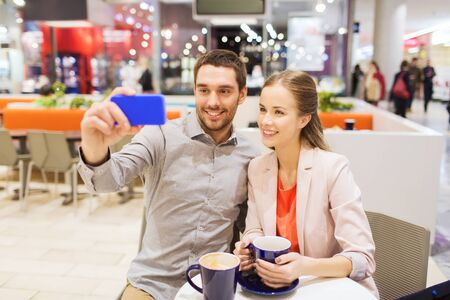 sale, shopping, consumerism, technology and people concept - happy young couple with smartphone taking selfie at cafe in mall photo