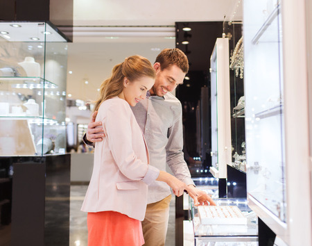 consumerism: sale, consumerism, shopping and people concept - happy couple choosing engagement ring at jewelry store in mall Stock Photo