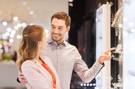 anillo de compromiso: venta, el consumismo y el concepto de la gente - los pares felices que apunta el dedo a la ventana de compras en la tienda de joyería en centro comercial